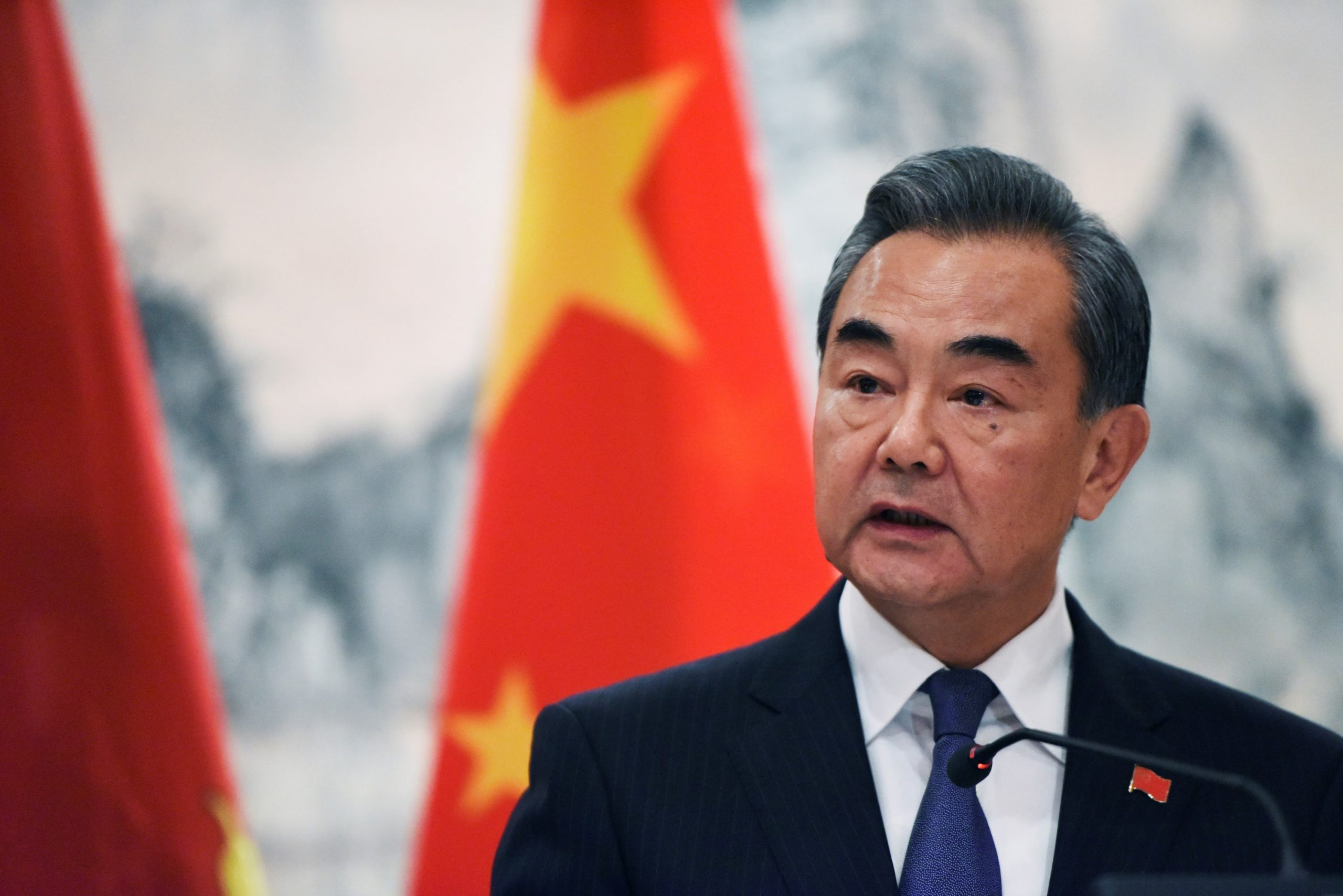 China's foreign minister says at symposium the US has successively angered and suppressed China
